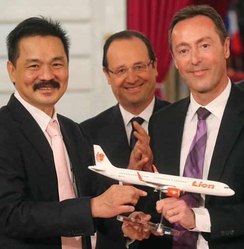 Airbus 320 model to CEO of Lion, Indonesian Air Rusdi Kirana, left, and CEO of Airbus, French Fabrice Bregier, right, and pose with a Airbus 320 model for the media while France's President Francois Hollande stands behind during a signing ceremony at the Elysee Palace in Paris, Monday, March 18, 2013.  Indonesian airline Lion Air is to buy 234 short to medium range aircraft from Airbus for 18.4 billion Euro($24 billion), in what is being billed as the biggest civilian deal in the history of the aircraft manufacturer. The contract was announced Monday at the French presidential palace, a sign of the deal's importance to the government. Airbus said it would secure 5,000 jobs at a time when French unemployment hovers around the 10 percent mark. (AP Photo/Michel Euler)