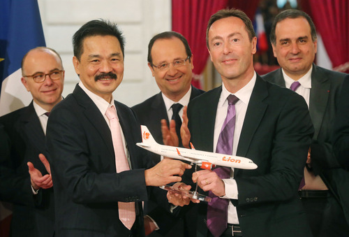 CEO of Lion,Air Rusdi Kirana of Indonesia, left, and CEO of Airbus, Frenchman Fabrice Bregier, right,  pose with a Airbus 320 model for the media while France's President Francois Hollande stands behind during a signing ceremony at the Elysee Palace in Paris, Monday, March 18, 2013.  Indonesian airline Lion Air is to buy 234 short to medium range aircraft from Airbus for 18.4 billion Euro($24 billion), in what is being billed as the biggest civilian deal in the history of the aircraft manufacturer. The contract was announced Monday at the French presidential palace, a sign of the deal's importance to the government. Airbus said it would secure 5,000 jobs at a time when French unemployment hovers around the 10 percent mark. (AP Photo/Michel Euler)
