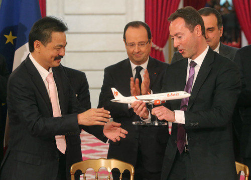 CEO of Airbus, French Fabrice Bregier, right, hands over an Airbus 320 model to CEO of Lion Air, Indonesian Rusdi Kirana, left, while France's President Francois Hollande stands behind during a signing ceremony at the Elysee Palace in Paris, Monday, March 18, 2013. Indonesian airline Lion Air is to buy 234 short to medium range aircraft from Airbus for 18.4 billion Euro($24 billion), in what is being billed as the biggest civilian deal in the history of the aircraft manufacturer. The contract was announced Monday at the French presidential palace, a sign of the deal's importance to the government. Airbus said it would secure 5,000 jobs at a time when French unemployment hovers around the 10 percent mark. (AP Photo/Michel Euler)