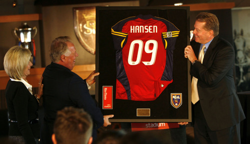Photo by Leah Hogsten  |  The Salt Lake Tribune Above, Real Salt Lake pro soccer team Chairman DaveChecketts (right) presents Del Loy Hansen with his own Real jersey. At left is Hansen's wife Lynnette Hansen.  Real Salt Lake pro soccer team Chairman Dave Checketts announced Wednesday that Utah entrepreneur and real estate developer Dell Loy Hansen has purchased a co-ownership in SCP Worldwide's Utah sports properties. Hansen will serve as Vice Chairman and Alternate Governor for REal Salt Lake.
