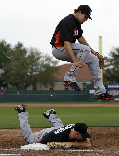 Miami Marlins starting pitcher Nate Eovaldi jumps over first baseman Kevin Kouzmanoff  who ducks after tagging the base to get Minnesota Twins' Justin Morneau out on a grounder in the fourth inning of an exhibition spring training baseball game in Fort Myers, Fla., Monday, March 18, 2013. (AP Photo/Elise Amendola)
