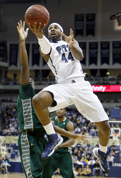 Pittsburgh's J.J. Moore (44) shoots over South Florida's Jawanza Poland in the first half of an NCAA college basketball game Wednesday, Feb. 27, 2013, in Pittsburgh. (AP Photo/Keith Srakocic)
