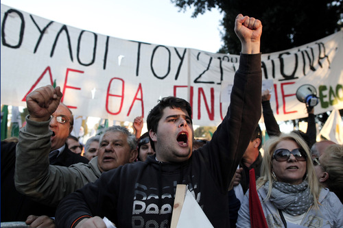 Protesters chant slogans outside the Cypriot parliament against a crucial parliamentary vote on a plan to seize a part of depositors' bank savings, in central Nicosia, Tuesday, March 19, 2013. The Cypriot government sought Tuesday to shield small savers from a plan that is intended to raise euro 5.8 billion ($7.5 billion) toward a financial bailout by seizing money from bank accounts. The plan, which is part of a larger bailout package being negotiated with other European countries, has been met with fury in Cyprus and has sent jitters across financial markets. (AP Photo/Petros Giannakouris)