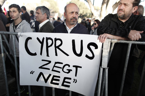"""Protester stand in front of a banner which reads """"Cyprus Says No"""" during a crucial parliamentary vote on a plan to seize a part of depositors' bank savings, in central Nicosia, Tuesday, March 19, 2013. The Cypriot government sought Tuesday to shield small savers from a plan that is intended to raise euro 5.8 billion ($7.5 billion) toward a financial bailout by seizing money from bank accounts. The plan, which is part of a larger bailout package being negotiated with other European countries, has been met with fury in Cyprus and has sent jitters across financial markets. (AP Photo/Petros Giannakouris)"""