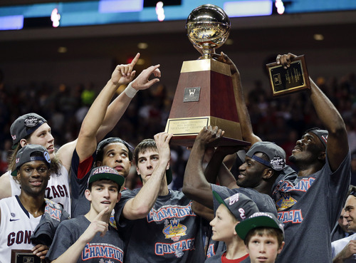 Gonzaga players hold up the championship trophy after winning the WCC title game. Zags have given other mid-major schools a blueprint for how to build a national program and make regular NCAA Tournament appearances. (AP Photo/Julie Jacobson)