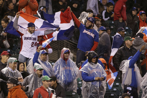 Fans of the Dominican Republic cheer after pitcher Samuel Deduno struck out Puerto Rico's Angel Pagan during the fifth inning of the championship game of the World Baseball Classic in San Francisco, Tuesday, March 19, 2013. (AP Photo/Eric Risberg)