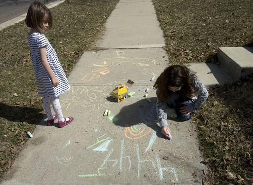 Kim Raff  |  The Salt Lake Tribune On a warm afternoon, neighbors (left) Clare Scarbrough and Abby Sagron color with chalk on the sidewalk outside of their homes on Emerson Avenue in Salt Lake City on Tuesday March 19, 2013.