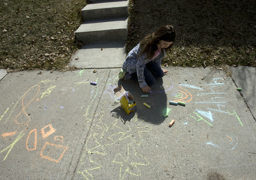 Kim Raff  |  The Salt Lake Tribune On a warm afternoon, Abby Sagron colors with chalk on the sidewalk outside of her home on Emerson Avenue in Salt Lake City on Tuesday March 19, 2013.