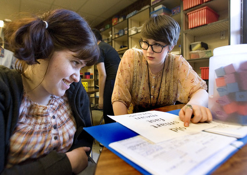Paul Fraughton     The Salt Lake Tribune Olympus High School junior Megan Jones, right, helps Cassie Kalmar with her language skills. Megan is one of several Olympus High students who volunteer at The Hartvigsen School for students with special needs.  Tuesday, March 12, 2013