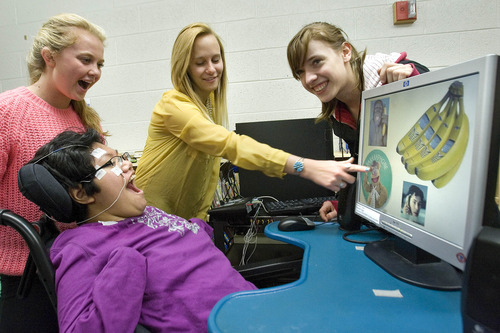 Paul Fraughton  |  The Salt Lake Tribune A team of Olympus High students, Lauren Anderson, Stephanie Hopkins and Amy Cummings, who volunteer at the Hartvigsen School, help Whitney Jasper use a new technology that allows her to navigate a computer screen with her eyes. Whitney reacts with excitement as she plays a game on the screen.