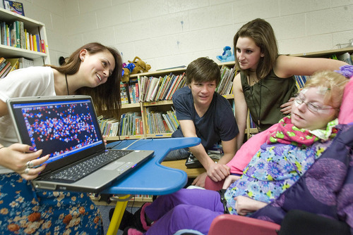 Paul Fraughton  |  The Salt Lake Tribune A team of Olympus High students, Emily Hoffman, Porter Treanor, and Sarah Demers, who volunteer at the Hartvigsen School, help Krystal Caldwell use a new technology that allows her to navigate a computer screen with her eyes. Krystal is filling the screen with stars using her eyes to place them.