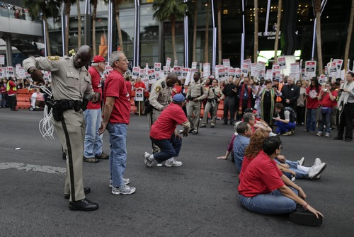A Las Vegas Metropolitan Police officer arrests a protestor during a civil disobedience demonstration by Culinary Union workers outside the Cosmopolitan Hotel-Casino, Wednesday, March 20, 2013, in Las Vegas. Nearly 98 protestors were arrested during the demonstration in which they sat on and blocked traffic along Las Vegas Boulevard. Workers have been in contract talks with Cosmopolitan Las Vegas owner Deutsche Bank for two years.  (AP Photo/Julie Jacobson)