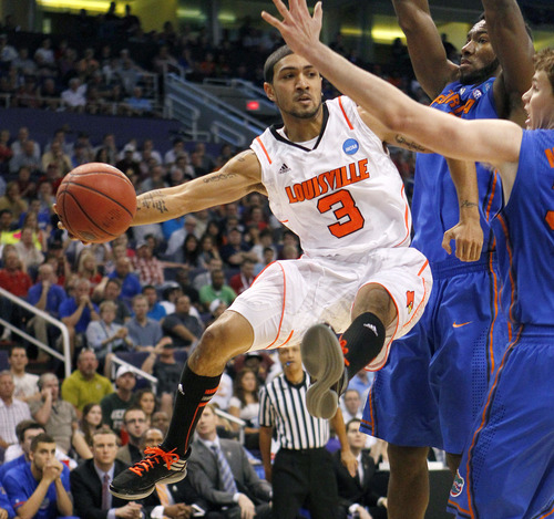 Louisville's Peyton Siva (3) moves the ball against Florida defenders Patric Young, second from right, and Erik Murphy during the first half of an NCAA tournament West Regional final college basketball game, Saturday, March 24, 2012, in Phoenix. (AP Photo/Matt York)