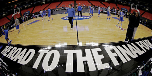 In this image taken with a fisheye lens, Kentucky head coach John Calipari, center, makes his way on the court during basketball practice, Thursday, March 22, 2012, in Atlanta.  Kentucky played Indiana in an NCAA tournament South Regional semifinal college basketball game. (AP Photo/David J. Phillip)