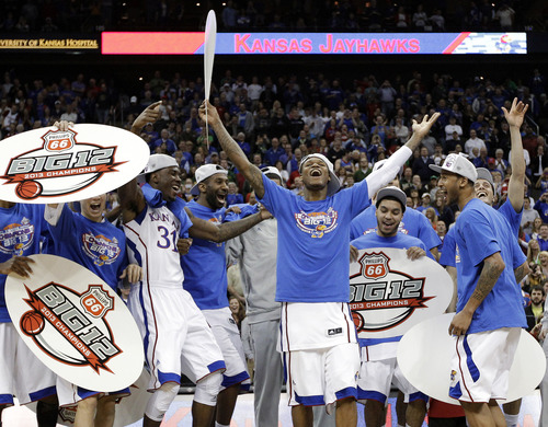 Kansas players celebrate after winning the Big 12 men's tournament title game against Kansas State on Saturday, March 16, 2013, in Kansas City, Mo. Kansas won the NCAA college basketball game 70-54. (AP Photo/Charlie Riedel)