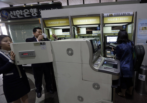 Two bank clerks, left, check an automated teller machine at a branch of Shinhan Bank after the bank's computer networks are fixed in Seoul, South Korea, Wednesday, March 20, 2013. Computers networks at two major South Korean banks and three top TV broadcasters went into shutdown mode en masse Wednesday, paralyzing bank machines across the country and prompting speculation of a cyberattack by North Korea. (AP Photo/Lee Jin-man)