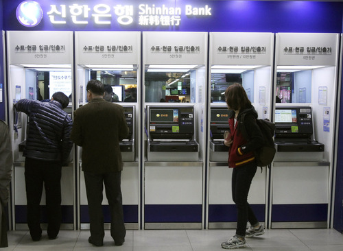 Depositors try to use automated teller machines of Shinhan Bank while the bank's computer networks are paralyzed at a subway station in Seoul, South Korea, Wednesday, March 20, 2013. Computer networks at two major South Korean banks and three top TV broadcasters went into shutdown mode en masse Wednesday, paralyzing bank machines across the country and prompting speculation of a cyberattack by North Korea. (AP Photo/Ahn Young-joon)