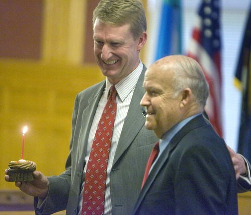 Paul Fraughton | Tribune file photo Kirk Jowers, director of the Hinckley Institute of Politics, presents a birthday cupcake to pollster Dan Jones in recognition of his 75th birthday in 2009.