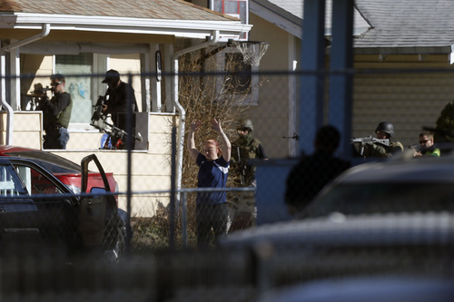 Chris Detrick     The Salt Lake Tribune Law enforcement officers take a suspect into custody near the scene of a shooting at 1159 S. Foulger Street Tuesday March 19, 2013. The shooting occurred as members of the Joint Criminal Apprehension Team surrounded a home in the area of 1100 South between State and Main streets.