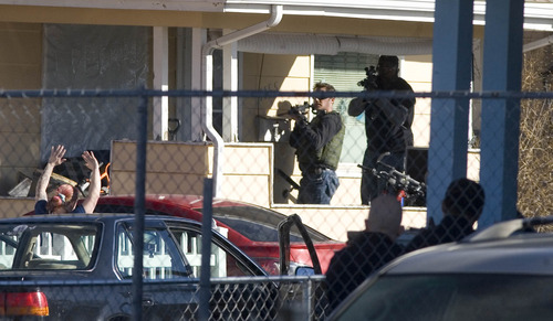Paul Fraughton      Salt Lake Tribune  With their guns trained on her, police direct a woman as she exits a house on Foulger Street between State and Main.  Tuesday, March 19, 2013