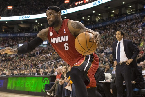 FILE - Miami Heat's LeBron James drives at the Toronto Raptors' defence as Heat's Head Coach Erik Spoelstra looks on during first half NBA basketball action in Toronto on in this March 17, 2013 file photo. Jerry West, Wilt Chamberlain and Goodrich were a Big Three to rival what Miami has, the core of a team that racked up routs on the way to an NBA-record 33 straight victories in the 1971-72 season. (AP Photo/The Canadian Press, Chris Young)