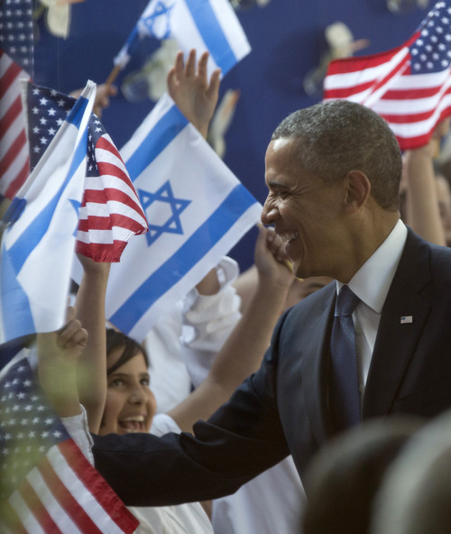 President Barack Obama is greeted by children waving Israeli and American flags as he arrives at the residence of Israeli President Shimon Peres, Wednesday, March 20, 2013, in Jerusalem. (AP Photo/Carolyn Kaster)