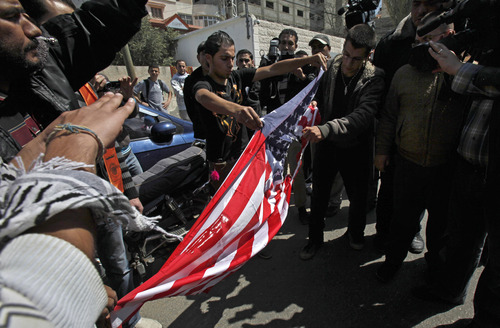 Palestinians rip an American flag during a protest against the visit of the U.S. President Barack Obama in Gaza City, Wednesday, March 20, 2013. Obama arrived Wednesday in Israel for his first visit to the country, and only his second to the Middle East, outside of a quick jaunt to Iraq, since taking office. He will also be making his first trips as president to the Palestinian Authority and Jordan this week. (AP Photo/Adel Hana)