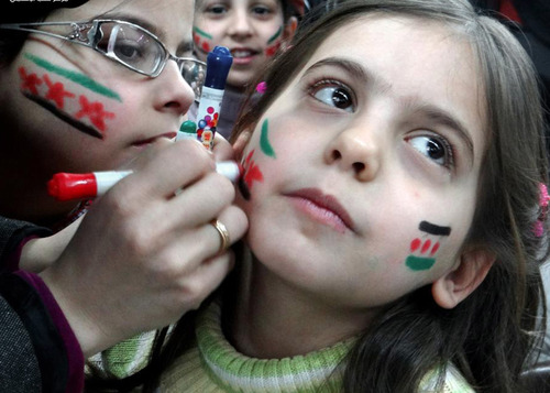 In this citizen journalism image provided by Aleppo Media Center AMC which has been authenticated based on its contents and other AP reporting, Syrian girls paint their faces with colors of the Syrian revolutionary flag during a fesitval, in Aleppo, Syria, Wednesday March 20, 2013. Syria's main opposition group demanded Wednesday a full international investigation into an alleged chemical weapons attack in the country's north, calling for a team to be sent to the village where it reportedly occurred. (AP Photo/Aleppo Media Center, AMC)