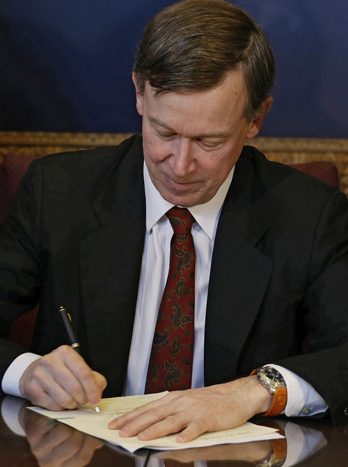 Colorado Gov. John Hickenlooper signs the state's gun control bills into law at the Capitol in Denver on Wednesday, March 20, 2013. The bills place new restrictions on firearms and signal a change for Democrats who traditionally shied away from the gun control debate in Colorado. (AP Photo/Ed Andrieski, Pool)