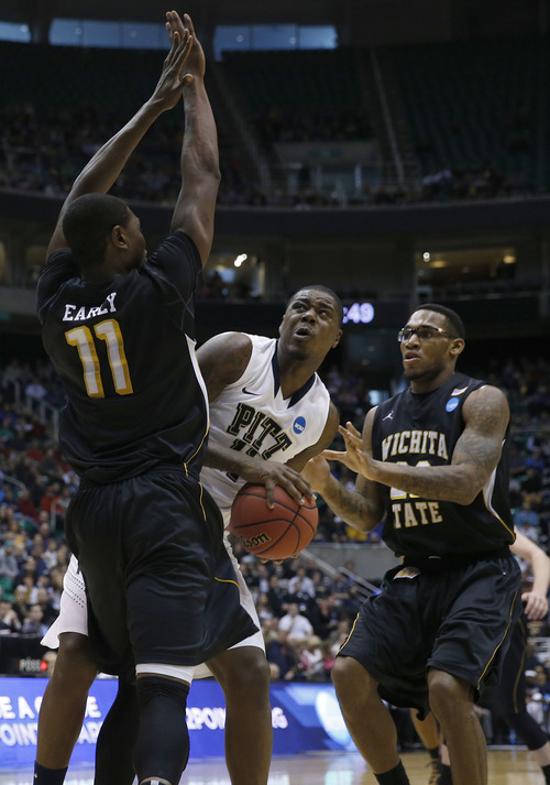 Chris Detrick  |  The Salt Lake Tribune  Pittsburgh Panthers forward Dante Taylor (11) is defended by Wichita State Shockers forward Cleanthony Early (11) and Wichita State Shockers forward Carl Hall (22) as the Panthers face the Shockers in the NCAA tournament at EnergySolutions Arena on Thursday, March 21, 2013.