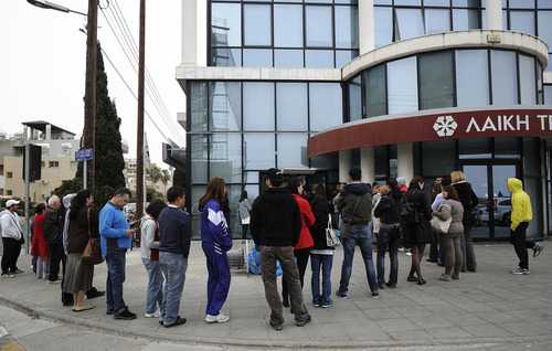 People wait to use the ATM of a closed branch of Laiki Bank in southern port city of Limassol, Thursday, March 21, 2013. The European Central Bank says it will keep emergency aid for Cyprus' troubled banks in place at least until Monday but will have to cut it off after that unless an international rescue program is drawn up. (AP Photo/Pavlos Vrionides)