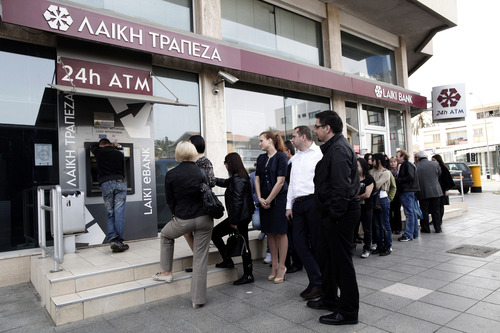 People queue at an ATM outside a closed Laiki Bank branch in capital Nicosia, Cyprus, Thursday, March 21, 2013. The European Central Bank says it will keep emergency aid for Cyprus' troubled banks in place at least until Monday but will have to cut it off after that unless an international rescue program is drawn up. (AP Photo/Petros Giannakouris)