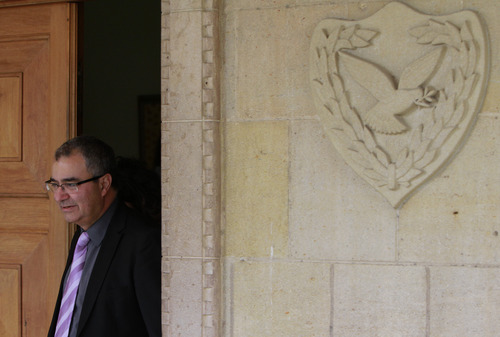 Cyprus' Central Bank chief Panicos Demetriades leaves after the meeting outside the presidential palace in capital Nicosia, Thursday March 21, 2013. The European Central Bank says it will keep emergency aid for Cyprus' troubled banks in place at least until Monday but will have to cut it off after that unless an international rescue program is drawn up. (AP Photo/Petros Karadjias)