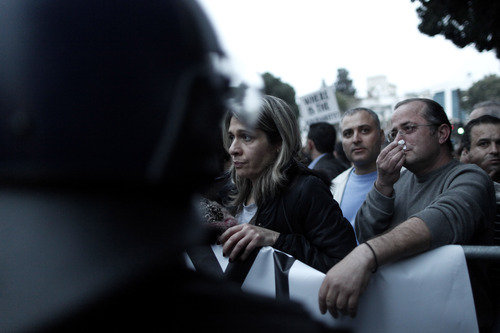 An employee of Laiki bank reacts outside the Cypriot parliament during an anti-bailout rally, Nicosia, Thursday, March 21, 2013. Cypriot officials were scrambling Thursday to cement a revised plan to raise funds demanded by international creditors in exchange for an international bailout Thursday, with time running out fast and the country's economy just days away from potential ruin. (AP Photo/Petros Giannakouris)