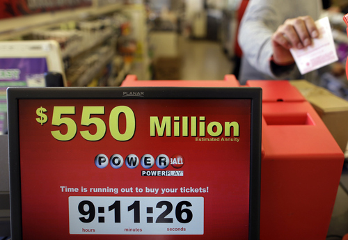 Store clerk Keyur Patel pulls a Powerball ticket that was dispensed from a machine in a convenience store in Baltimore, Wednesday, Nov. 28, 2012. There have been no Powerball winners since Oct. 6, and the jackpot has grown into the second highest in lottery history, behind only the $656 million Mega Millions prize in March. (AP Photo/Patrick Semansky)