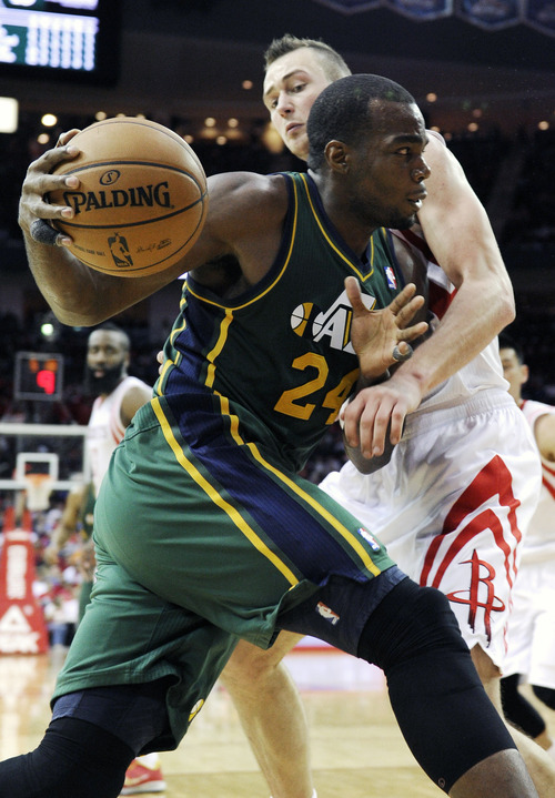 Utah Jazz's Paul Millsap (24) pushes past Houston Rockets' Donatas Motiejunas, right, in the second half of an NBA basketball game on Wednesday, March 20, 2013, in Houston. The Rockets won 100-93. (AP Photo/Pat Sullivan)