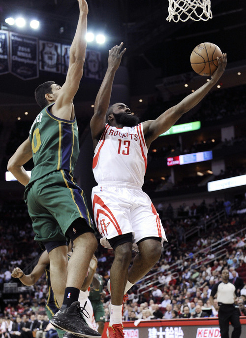 Houston Rockets' James Harden (13) goes to the basket in front of Utah Jazz's Enes Kanter (0) in the first half of an NBA basketball game on Wednesday, March 20, 2013, in Houston. (AP Photo/Pat Sullivan)