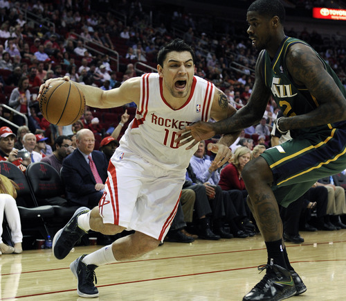 Houston Rockets' Carlos Delfino (10) drives the ball around Utah Jazz's Marvin Williams (2) in the first half of an NBA basketball game on Wednesday, March 20, 2013, in Houston. (AP Photo/Pat Sullivan)