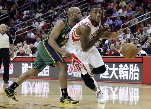 Utah Jazz's Jamaal Tinsley (6) knocks the ball away from Houston Rockets' Greg Smith (4) in the first half of an NBA basketball game on Wednesday, March 20, 2013, in Houston. (AP Photo/Pat Sullivan)