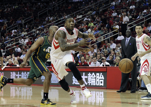Utah Jazz's Jamaal Tinsley (6) knocks the ball away from Houston Rockets' Thomas Robinson in the first half of an NBA basketball game Wednesday, March 20, 2013, in Houston. (AP Photo/Pat Sullivan)