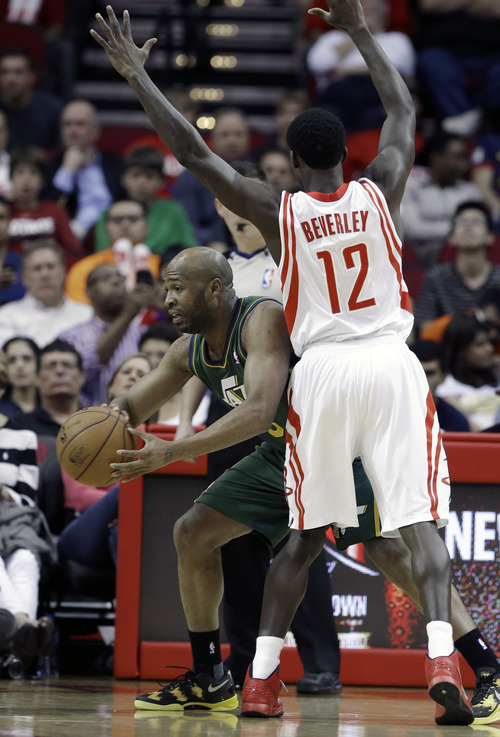 Utah Jazz's Jamaal Tinsley, left, tries to pass off the ball around Houston Rockets' Patrick Beverley (12) in the first half of an NBA basketball game on Wednesday, March 20, 2013, in Houston. (AP Photo/Pat Sullivan)