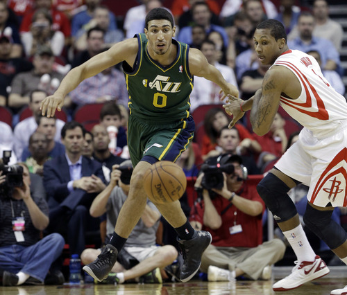 Utah Jazz's Enes Kanter (0) and Houston Rockets' Greg Smith, right, chase a loose ball in the first half of an NBA basketball game on Wednesday, March 20, 2013, in Houston. (AP Photo/Pat Sullivan)
