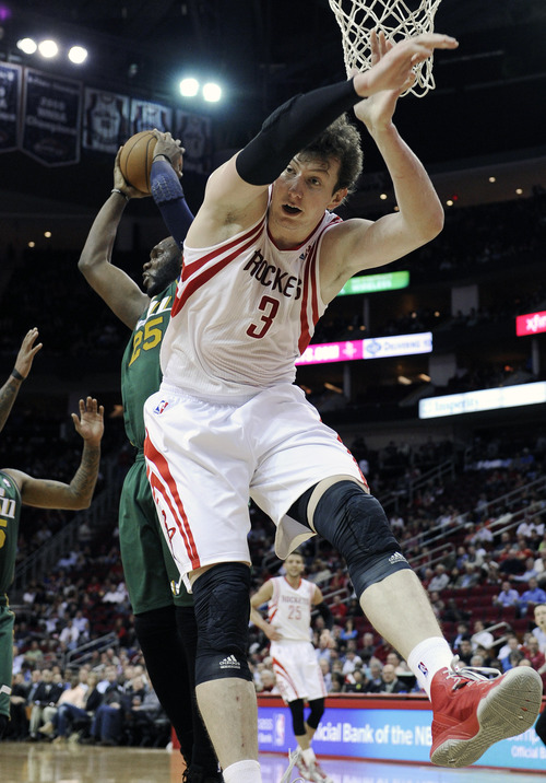 Utah Jazz's Al Jefferson (25) grabs a rebound away from Houston Rockets' Omer Asik (3) in the first half of an NBA basketball game on Wednesday, March 20, 2013, in Houston. (AP Photo/Pat Sullivan)