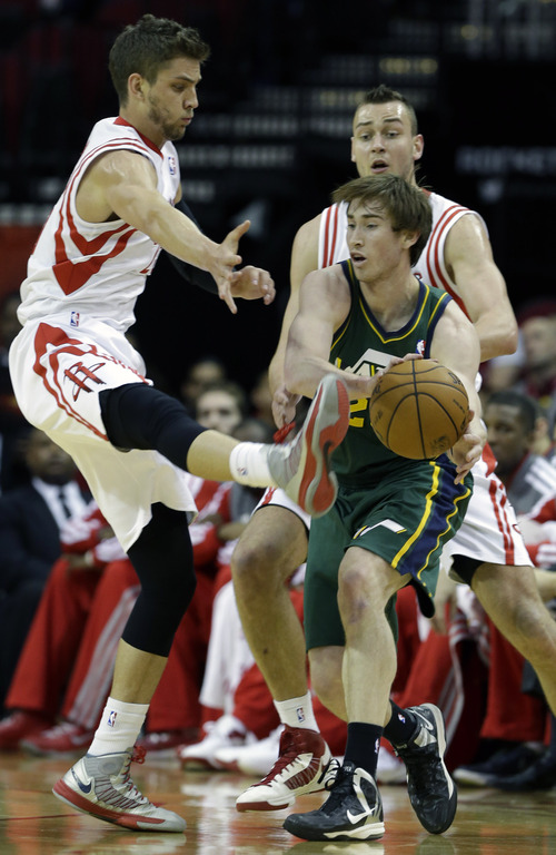 Houston Rockets' Chandler Parsons, left, tries to block a Utah Jazz's Gordon Hayward, center, pass with his foot as Rockets' Donatas Motiejunas looks on in the first half of an NBA basketball game on Wednesday, March 20, 2013, in Houston. (AP Photo/Pat Sullivan)