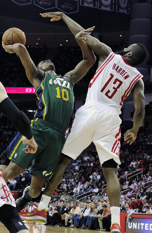Utah Jazz's Alec Burks (10) goes to the basket against Houston Rockets' James Harden (13) in the second half of an NBA basketball game on Wednesday, March 20, 2013, in Houston. The Rockets won 100-93. (AP Photo/Pat Sullivan)