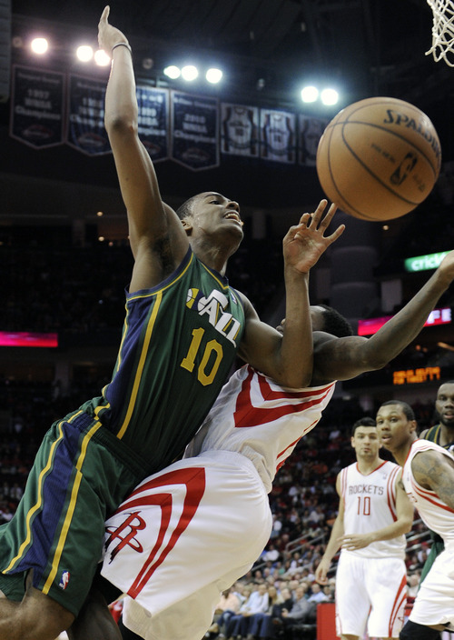 Utah Jazz's Alec Burks (10) falls into Houston Rockets' Patrick Beverley, right, on his way to the basket in the second half of an NBA basketball game on Wednesday, March 20, 2013, in Houston. The Rockets won 100-93. (AP Photo/Pat Sullivan)