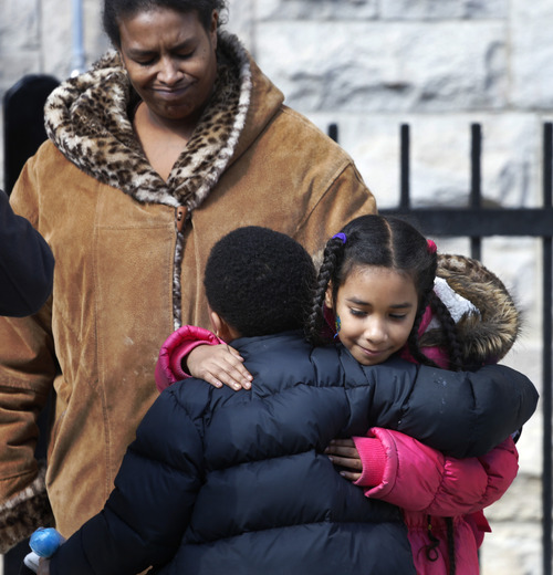 Maria Llanos, left, watches as her daughter Xochilt Fernandez hug a fellow student at the Lafayette School as school dismisses Thursday, March 21, 2013, in Chicago. Lafayette was one of several schools Chicago teachers, students and parents reacted with tears, questions and anger as news trickled out Thursday about which schools the city plans to close as part of a cost-cutting effort that opponents say will disproportionately affect minority children. (AP Photo/Charles Rex Arbogast)