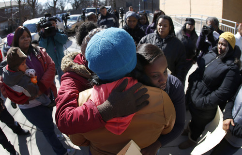 Parents of students at the Dumas Technology Academy Elementary School hug Yolanda Harris after she organized a  protest outside the school over the proposed closing of the Southside facility by the Chicago Board of Education, Friday, March 22, 2013, in Chicago. Chicago Public Schools officials ended months of speculation when they released the list of 54 schools the city plans to close, but the pushback against Mayor Rahm Emanuel and his schools chief is likely just starting to ramp up.(AP Photo/Charles Rex Arbogast)