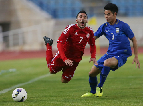 Thailand's Theerathon Bunmathan, right, attacks Lebanon's Hassan Maatouk, as they fight for the ball during the 2015 Asian Cup qualifier match, in Beirut, Lebanon, Friday March 22, 2013. Lebanon trounced Thailand 5-2 in a 2015 Asian Cup qualifier to give the country's football fans a much-needed morale boost after their sport was hit by a match-fixing scandal. (AP Photo/Hussein Malla)