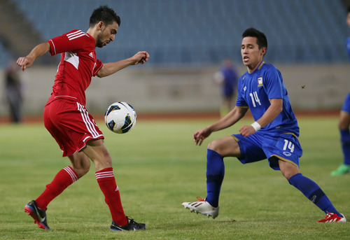 Lebanon's Mohammad Haidar, left, fights for the ball against Thailand's Anthony Ampaipitakwong, during the 2015 Asian Cup qualifier match, in Beirut, Lebanon, Friday March 22, 2013. Lebanon trounced Thailand 5-2 in a 2015 Asian Cup qualifier to give the country's football fans a much-needed morale boost after their sport was hit by a match-fixing scandal. (AP Photo/Hussein Malla)